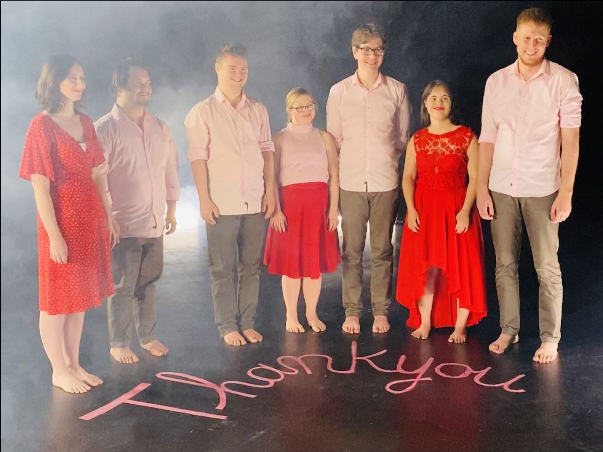 """Seven Restless Dancers smiling and standing above the words """"thank you"""" written on the stage"""
