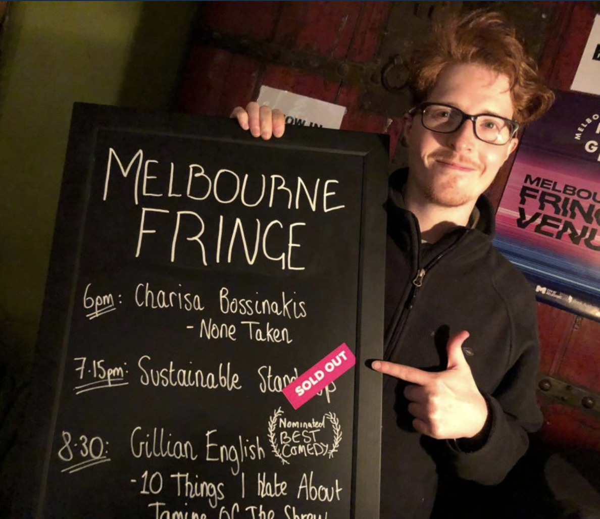 Maxwell Smith pointing at a blackboard advertising his show