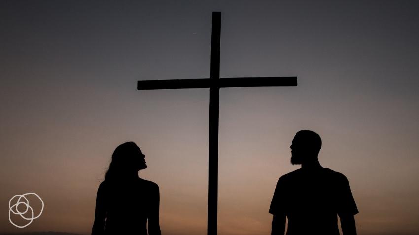 man & woman looking at a cross