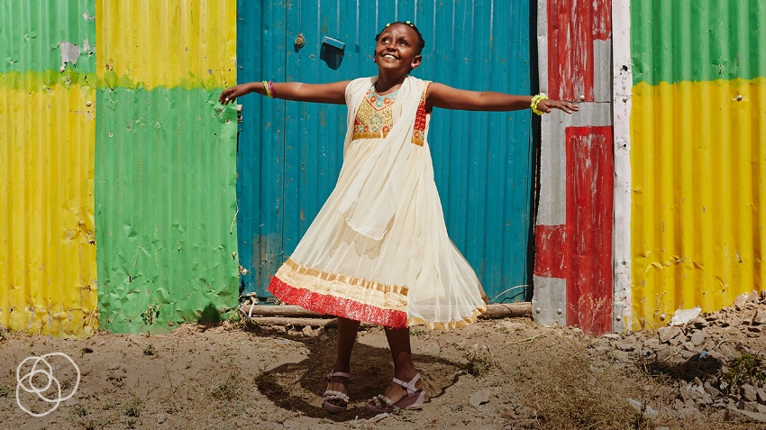 Girl dancing in front of colorful wall