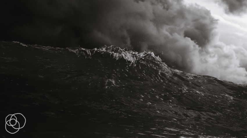 ocean wave under dark clouds