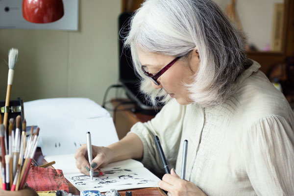 An older Asian woman with gray hair and glasses sits sketching at a table with three pens in her hands