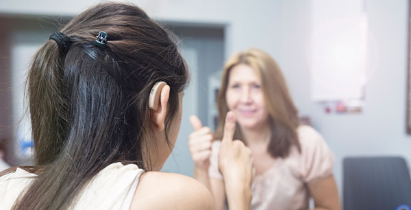 A young light-skinned woman with a hearing aid sits with her back to the camera and motions with a thumbs up to a white woman facing her, who is making the same movement