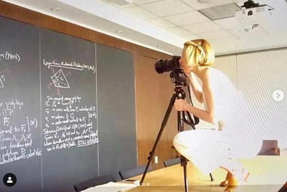 screenshot of FIT Instagram post using photo of professor Jessica Wynne taking photos of mathematician's chalkboard