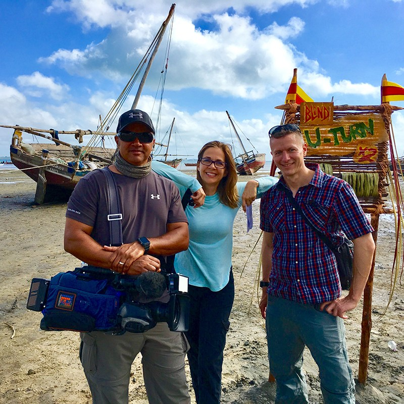 Elise Doganeri with a cameraman and producer in front of a shipwreck on a beach