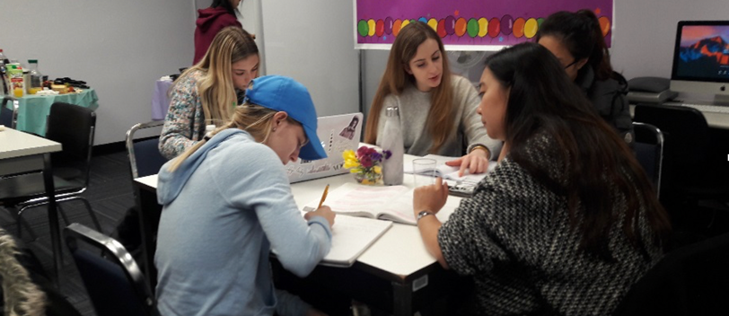 A group of tutors and students sitting around a table; helping each other.