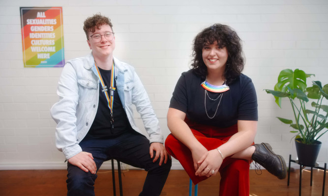 Two people seated, smiling into the camera, both wearing rainbow lanyards, pronoun badges and jewellery, in front of a wall with a poster reading 'All sexualities genders identities cultures welcome here'