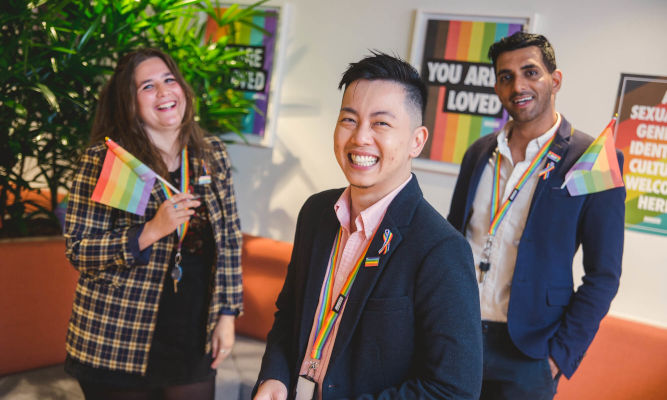 Three diverse people in business attire, wearing rainbow lanyards, ribbons and pins, standing in a corporate foyer in front of LGBTIQ advocacy posters, smiling with pride flags