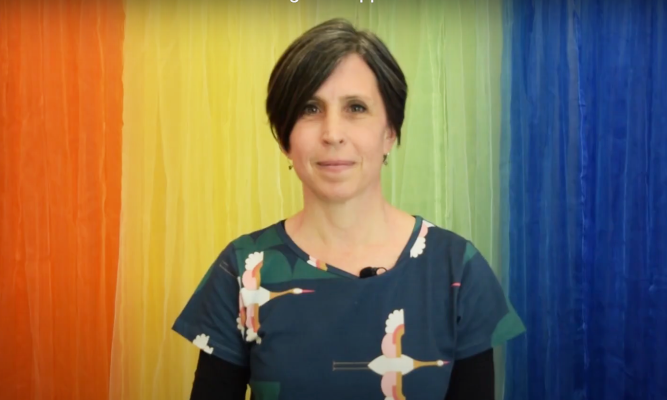 Rainbow Health Victoria Director Marina Carman stands smiling in front of a rainbow backdrop, wearing colourful clothes with a design of cranes flying.