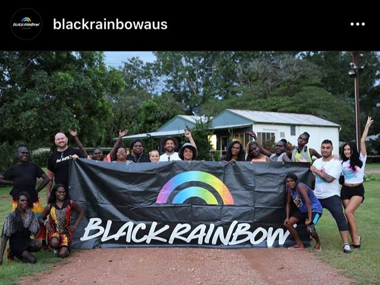 group of people holding black rainbow banner