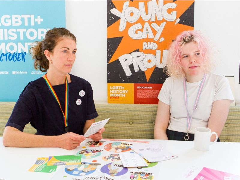A photo of two white women at a table with posters and papers on the table as if they were at a meeting together
