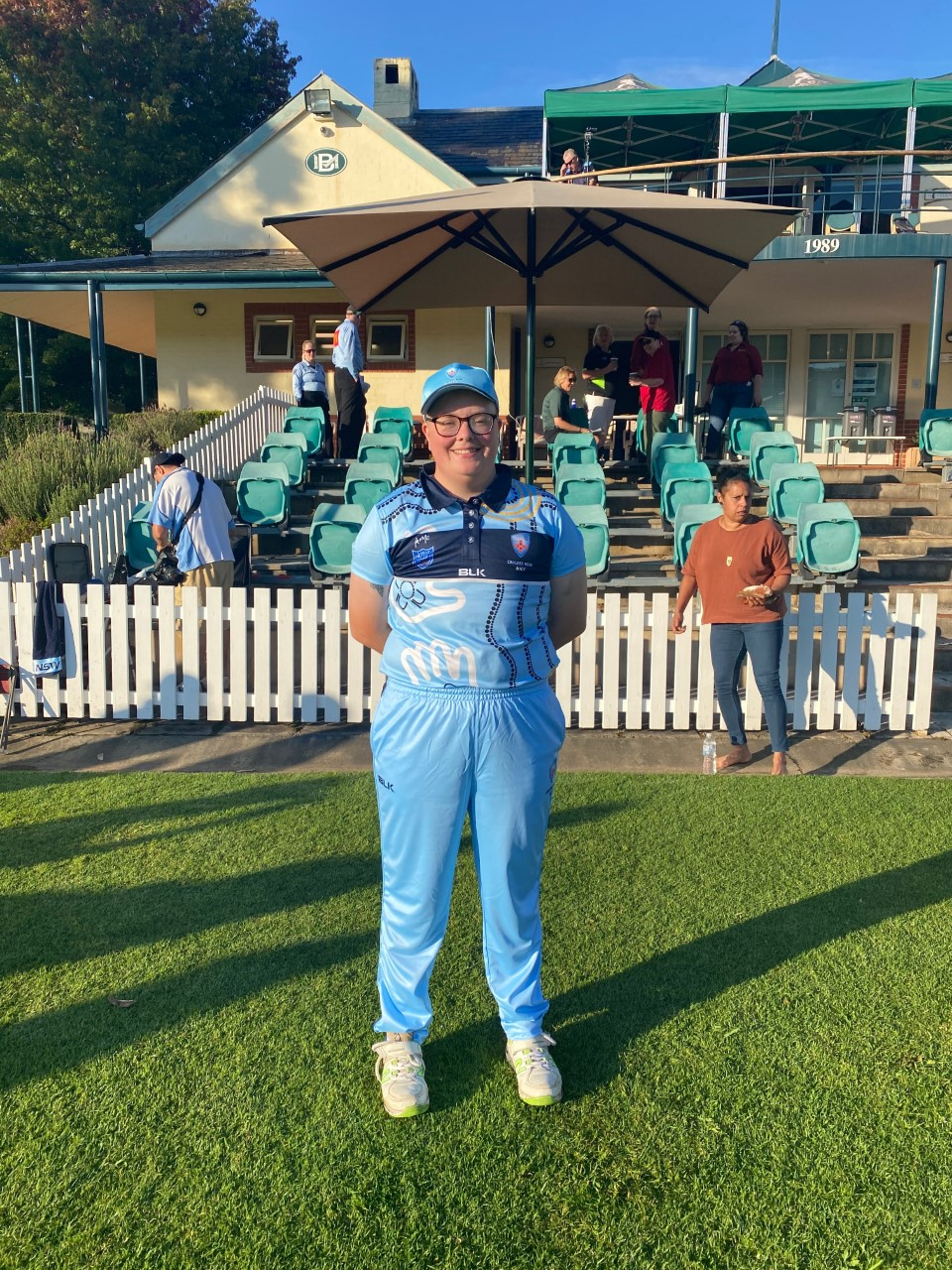 Taylor Ling stands on grass proudly in cricket uniform