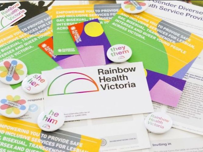 A post card promoting Rainbow Health Victoria on top of many other colourful postcard and flyer resources for the LGBTIQ communities. There are also colourful badges and pronoun badges scattered across these postcards.