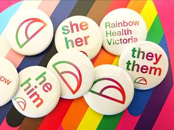 Pronoun badges over a colourful rainbow love heart background