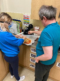 Photo credit: Leeds Autism Services - Learning disabled person preparing pizza with support worker