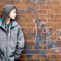 TES.com image of young boy in hoodie next to graffiti wall