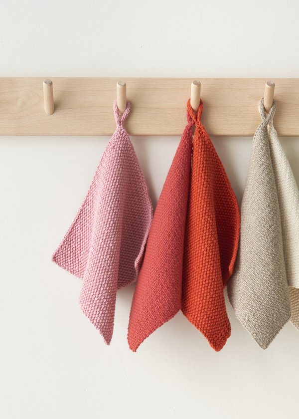 Three square washcloths hang on a row of wood pegs, in pink, coral and cream