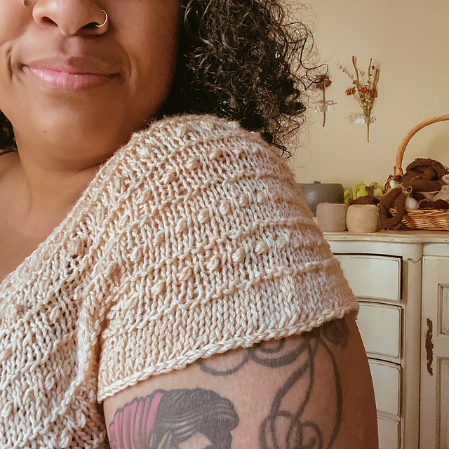 A hand knit shoulder of a short sleeve sweater with bobble pattern
