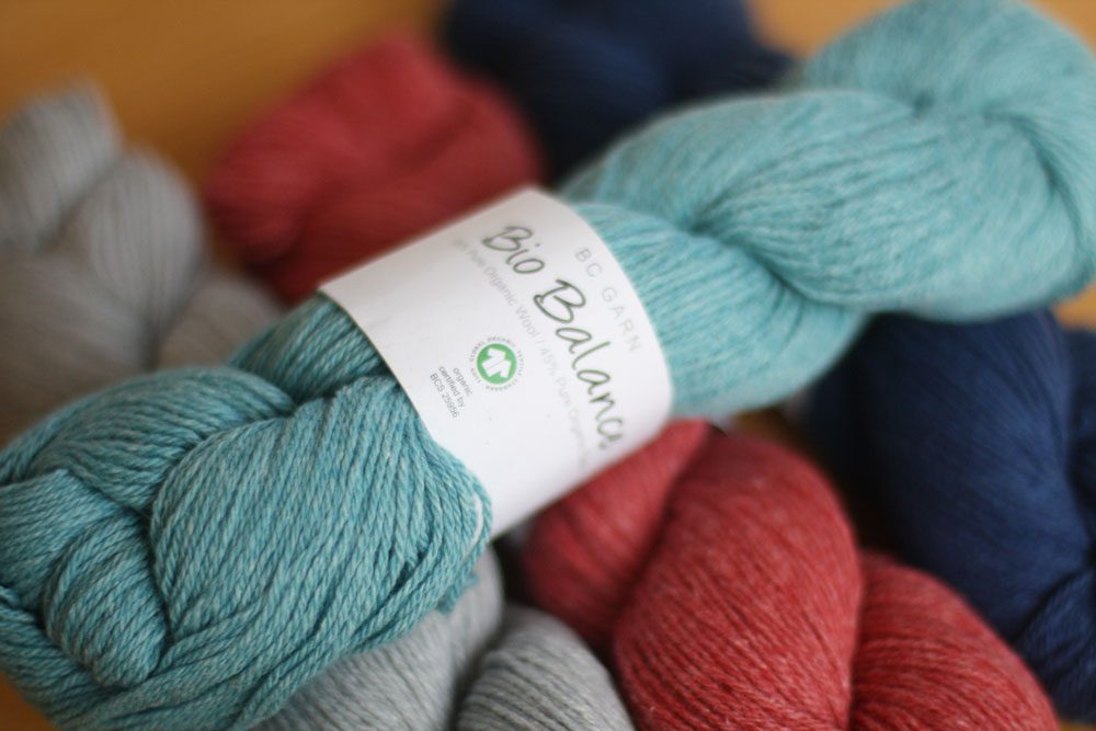 A skein of sky blue Bio Balance lies across a skein of silver, red and navy