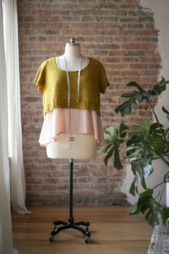 A short sleeve mustard knit tee on a mannequin in front of a brick wall