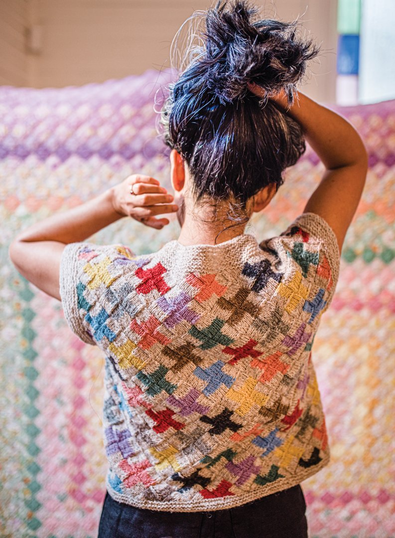 A back view of Lucky Pieces, an entrelac pattern making up a series of crosses on a light background