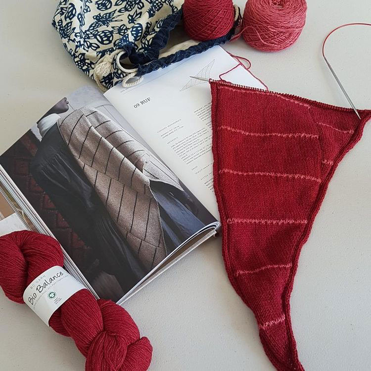 A red and pink striped shawl in progress, next to the open pattern page in 52 Weeks of Shawls