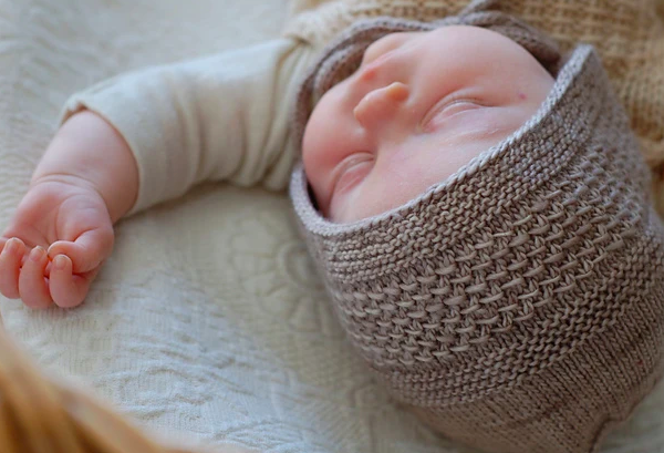 A small baby sleeps while wearing a silver textured knit bonnet