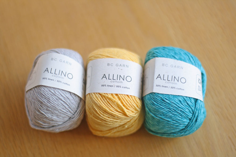 Three balls of Allino in silver, yellow and teal on a wood table