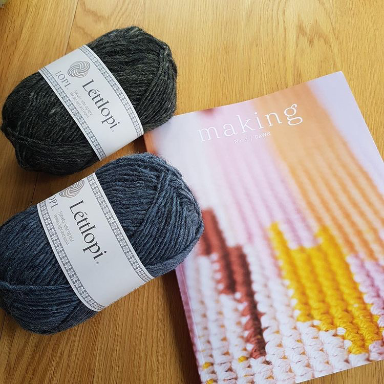 The cover of Dawn Making issue 11 and two balls of Lopi in grey-blue and dark green