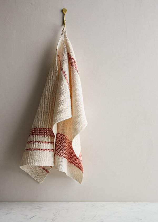 A natural white and red striped knit hand towel hanging on a cream wall