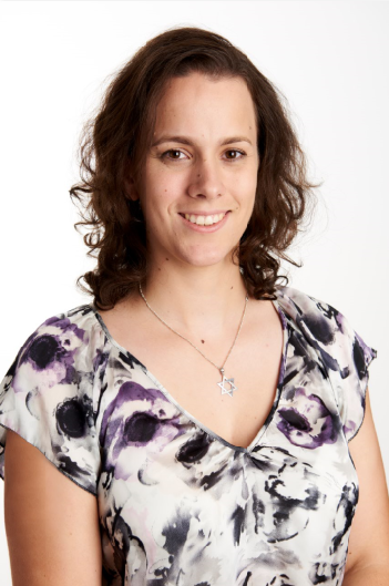 Photo of Christie, in a floral top with short brown hair, smiling