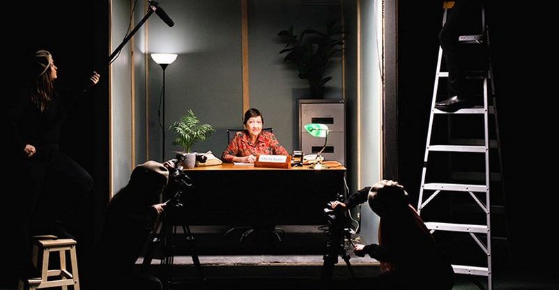 Image of a film set with a middle-aged woman at a desk with a name plate and lamp in an office, with lights, camera and crew members around her