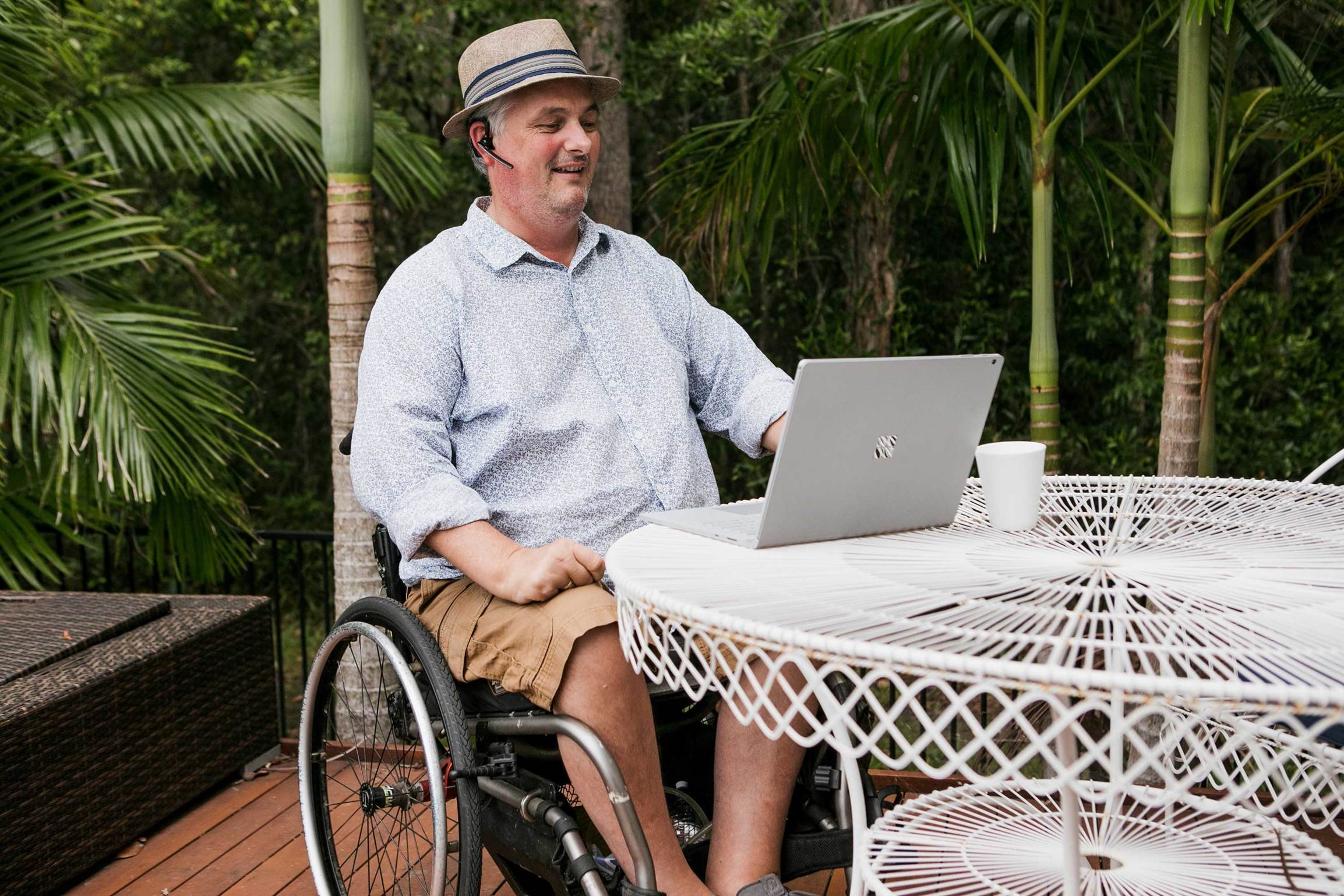 Cam in wheelchair with hat, outside on his laptop smiling