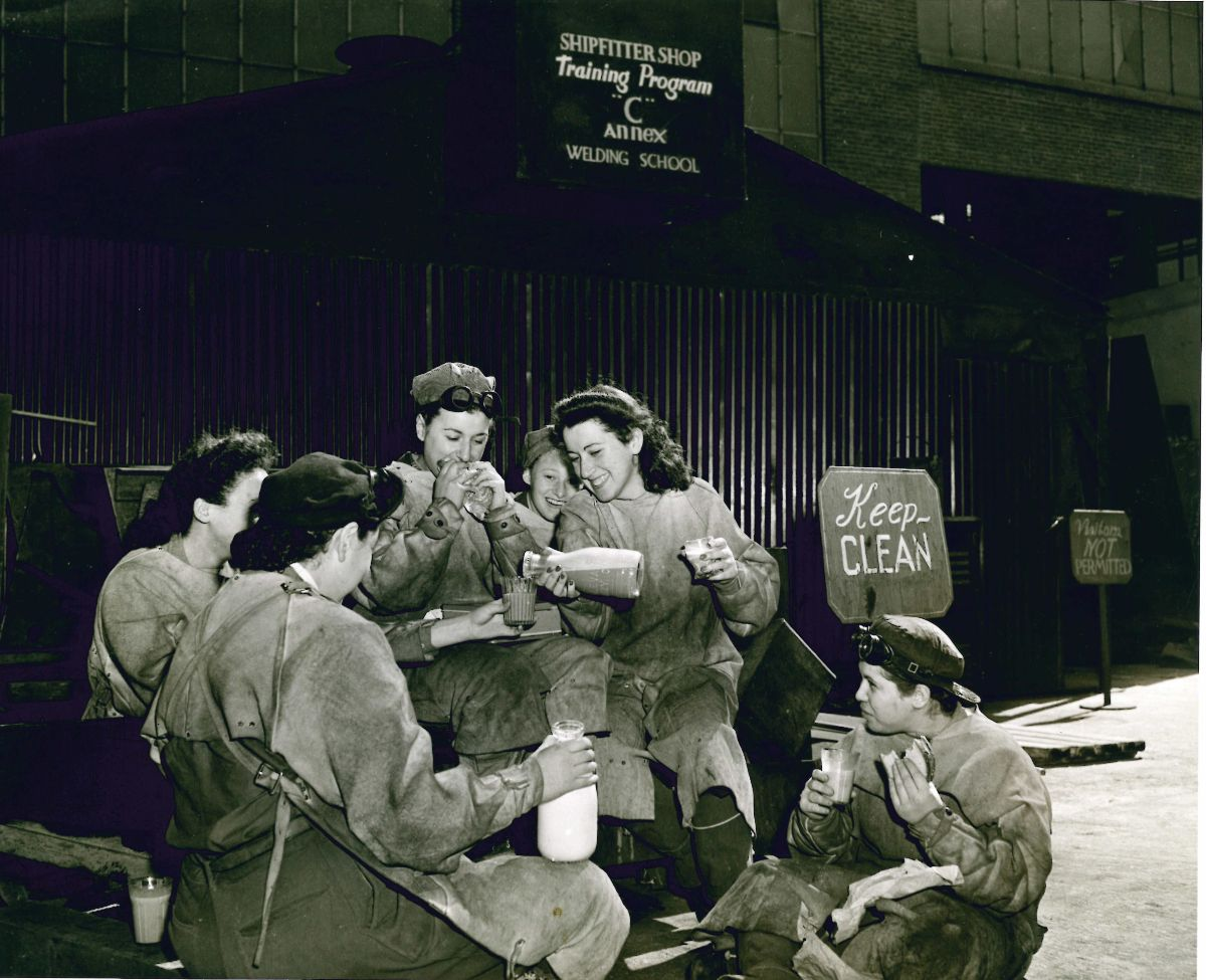 Black and white photograph of a group of women welders breaking for lunch