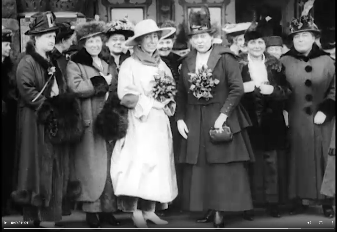 Black and white still photograph from newsreel stock. Jeannette Rankin stands in a white dress among several other women