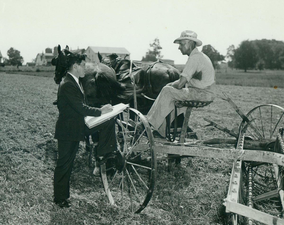 Black and white photograph of a man sitting on a tractor being pulled by horses. A man in a suit speaks to him and records answers