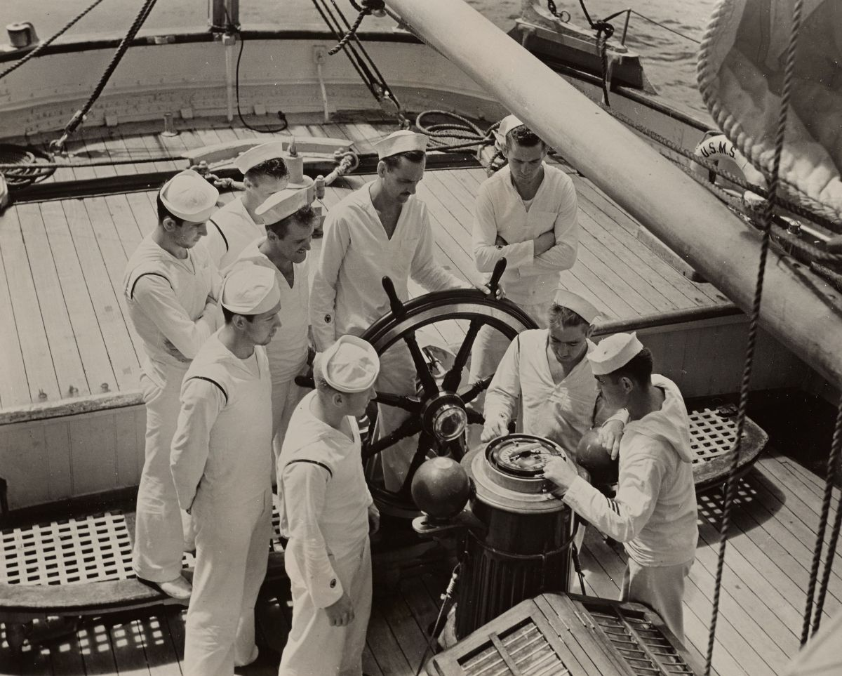 Black and white photograph of maritime service enrollees learning how to use a compass