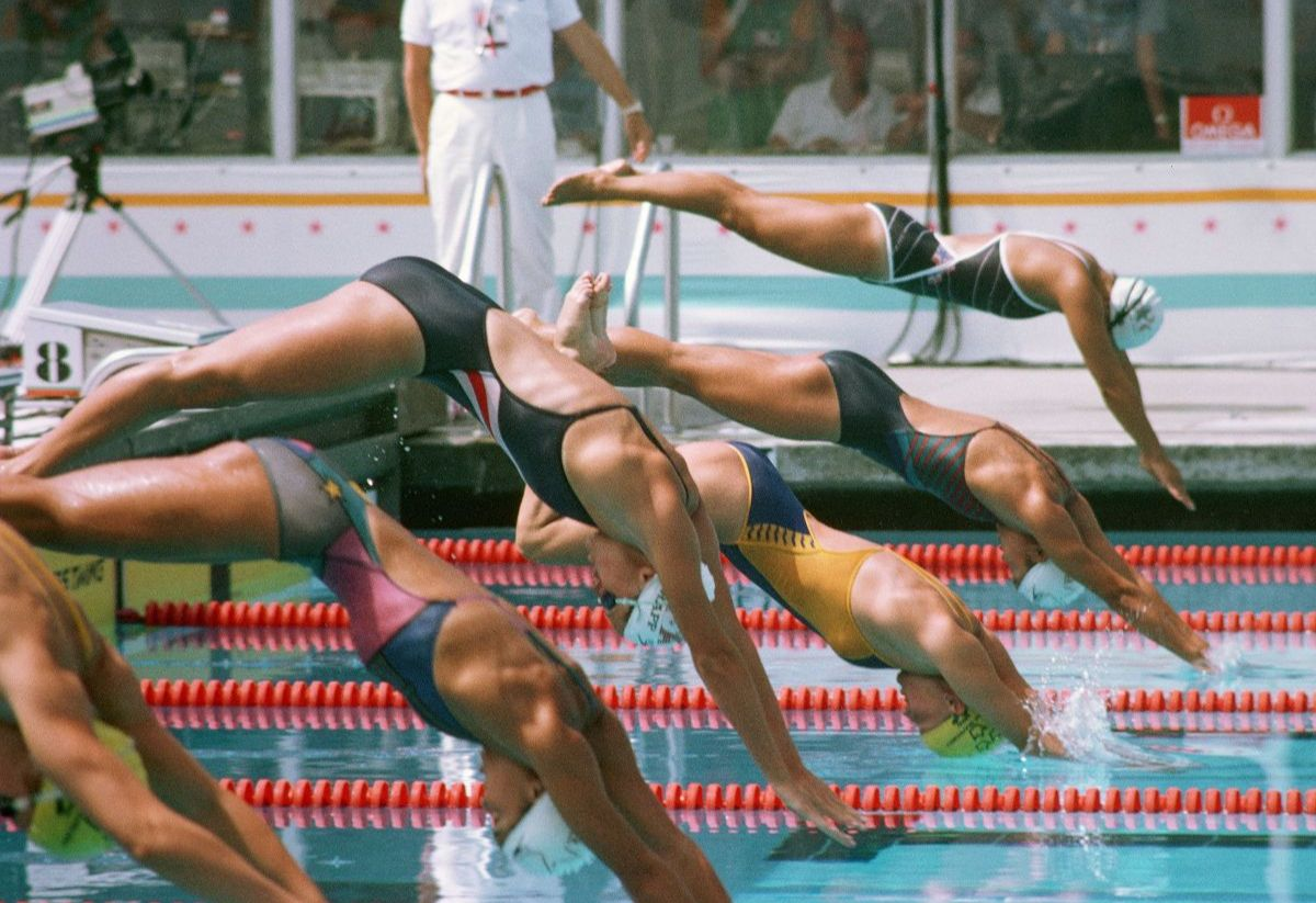 A group of women swimmers dive off the starting blocks