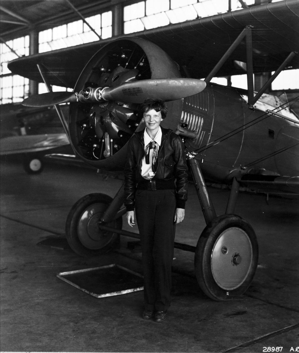 Photograph of Amelia Earhart standing in front of an airplane