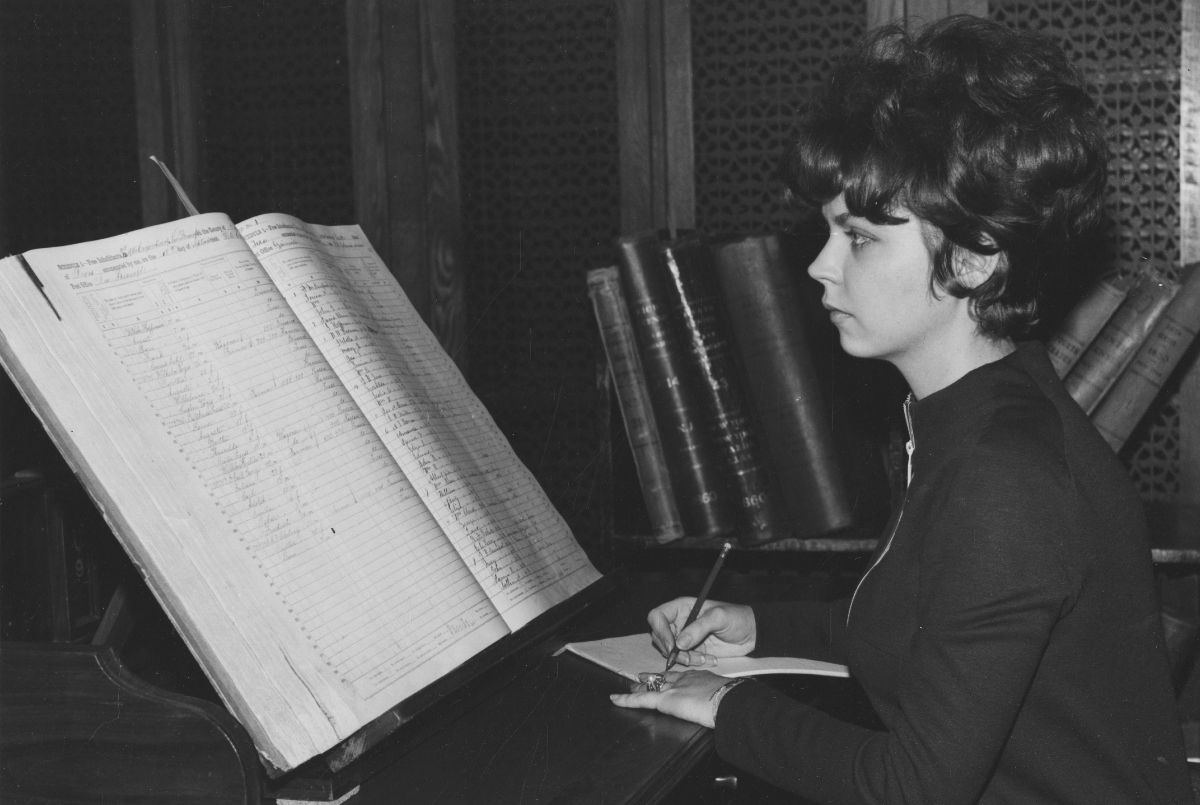 Black and white photograph of a woman in the National Archives research room looking at a book containing census population schedules and writing down notes
