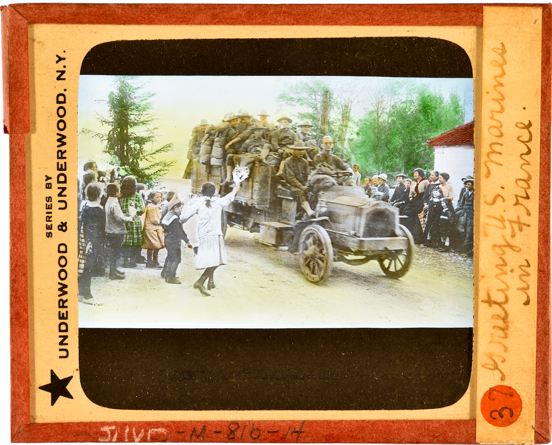 Slide showing car full of U.S. Marines driving down a road while a group of people watch and wave