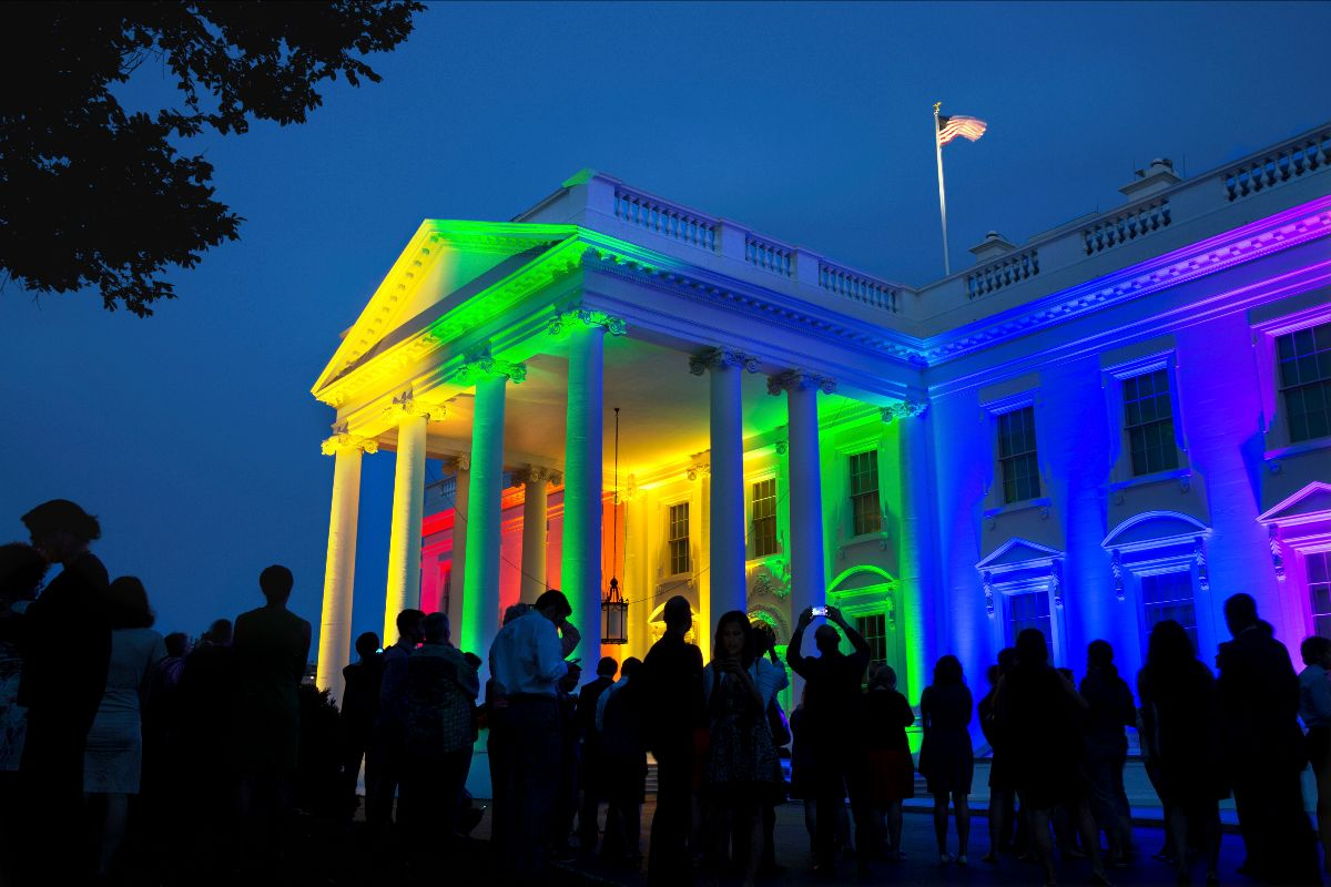 Photograph of the White House lit in rainbow colors. A crowd of people gather in front to look and take photos