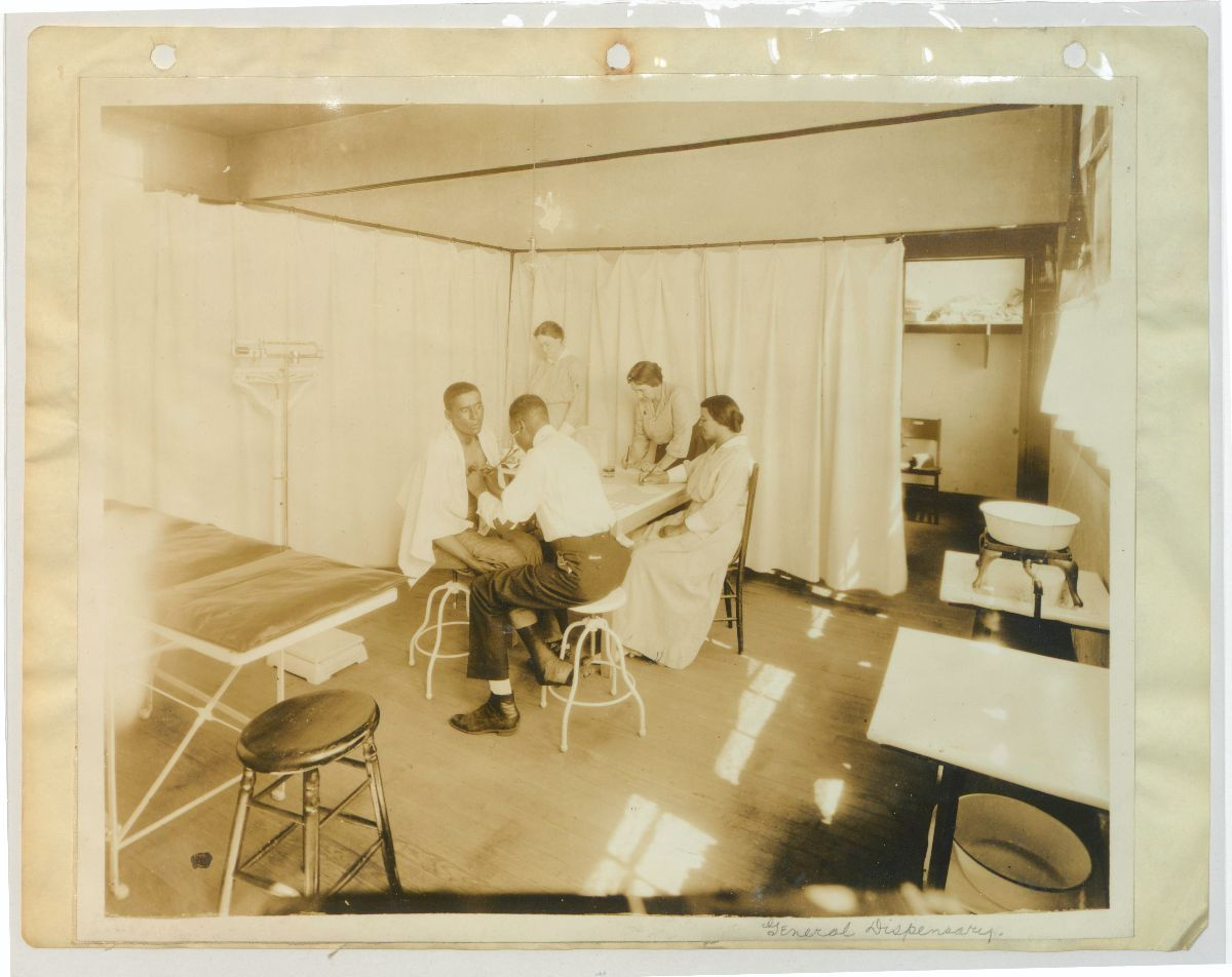 Black and white photograph of a man performing a medical exam on another man while three women look on
