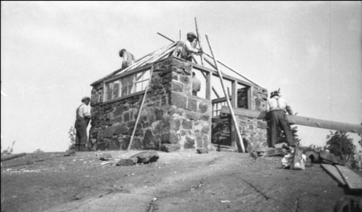 Black and white photograph of men constructing a stone house