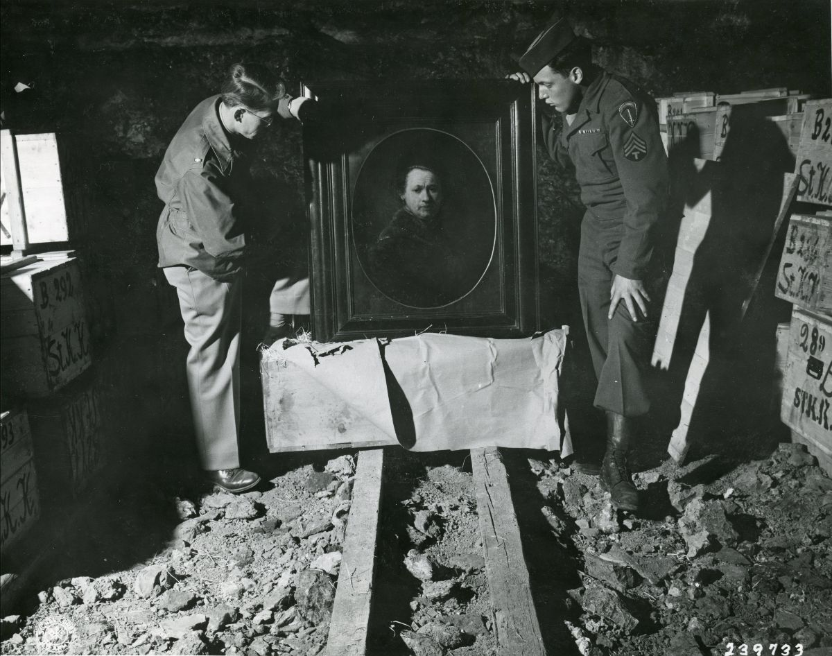 Black and white photograph of two soldiers inspecting a Rembrandt self portrait among looted art treasures