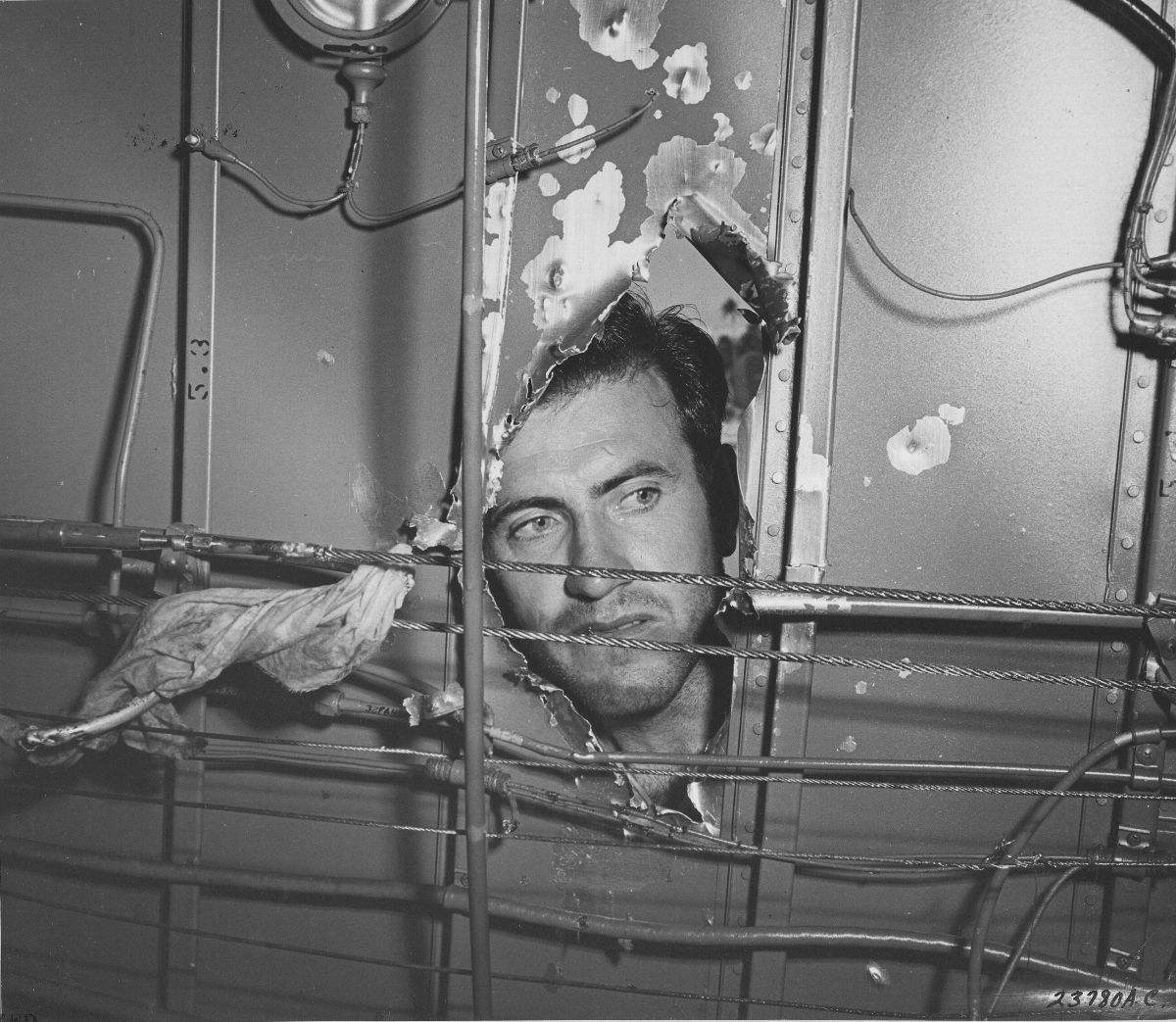 Photograph of Louis Zamperini examining a hole in his plane
