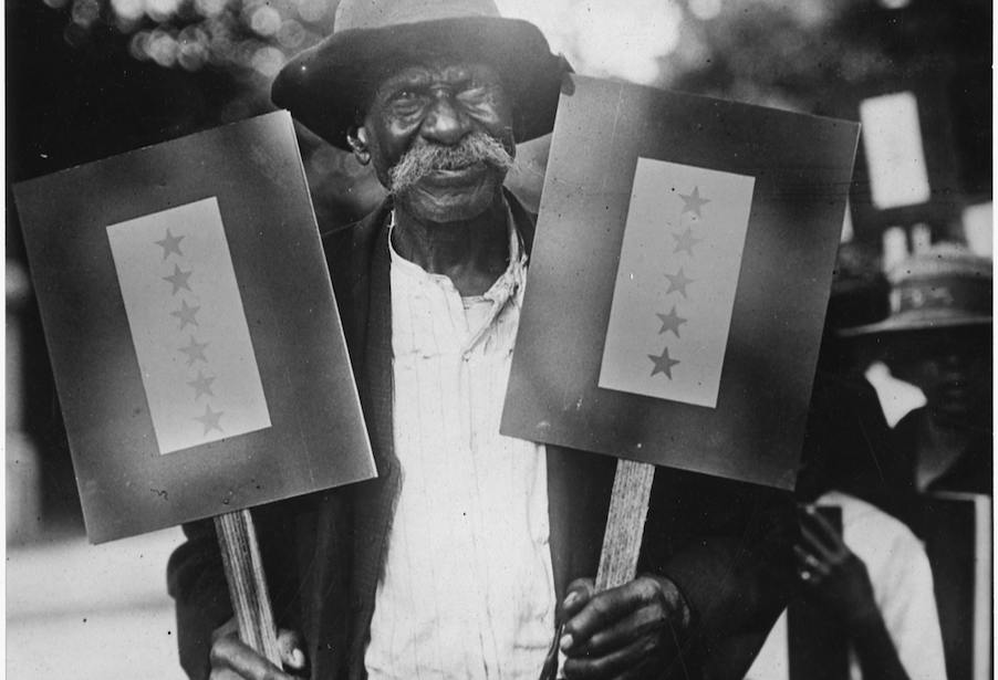 Black and white photograph of a man with a long mustache holding a sign in each hand. One sign contains 6 stars and the other sign contains 5 stars, representing his eleven sons in military service