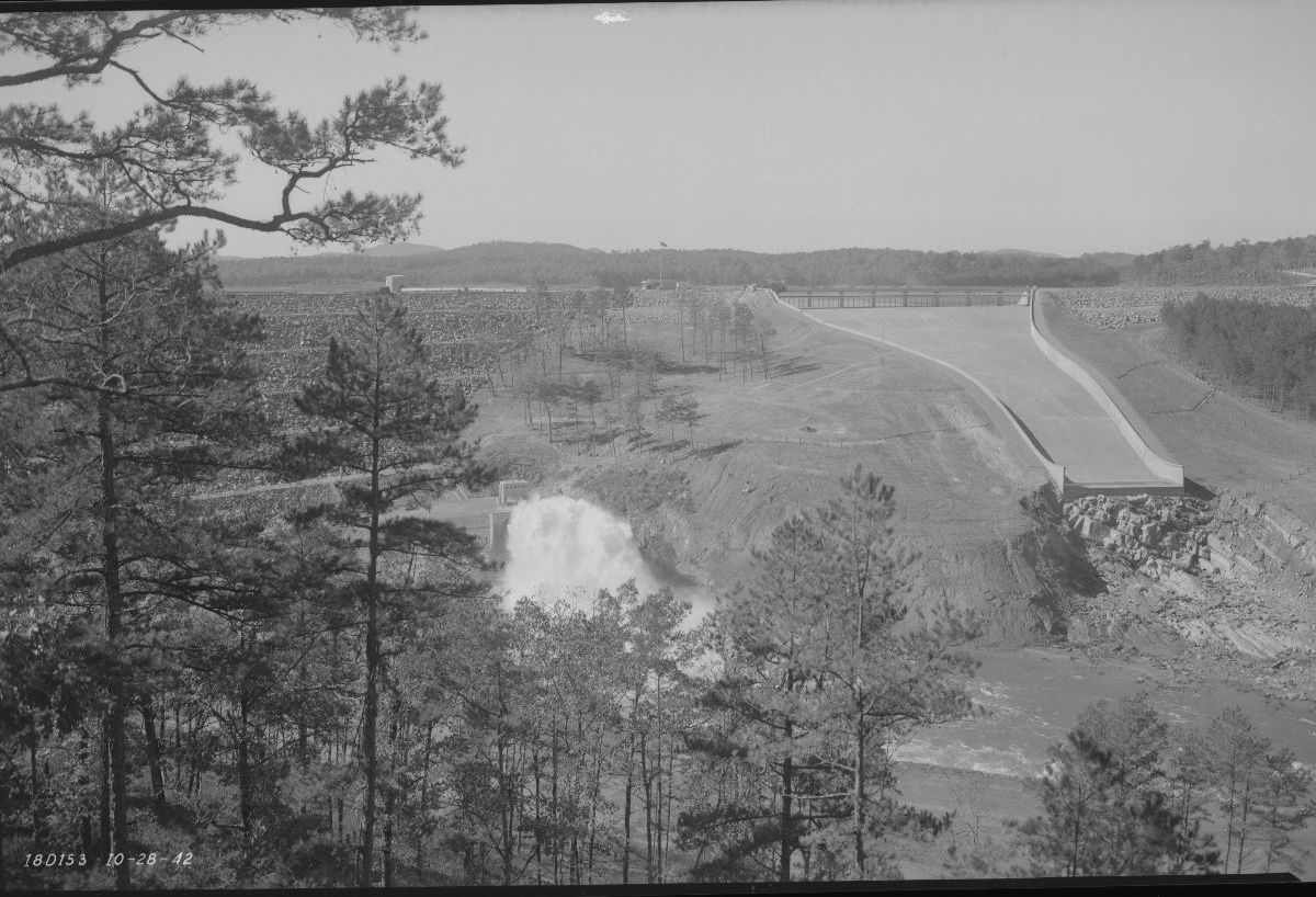 Black and white photograph of the tunnel outlet of the dam. Wooded area in the foreground of the photo.