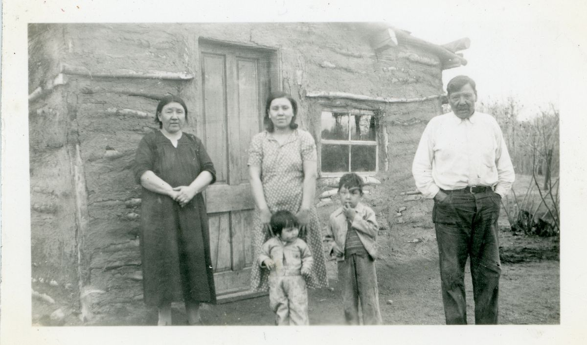 Black and white photo of a family standing in front of a stone house.