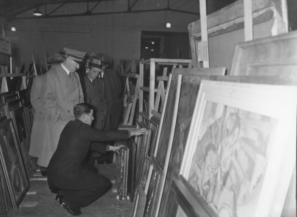 Black and white photograph of Adolf Hitler inspecting looted artwork